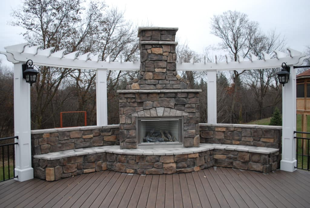 Stunning fireplace on a deck with a pergola accent