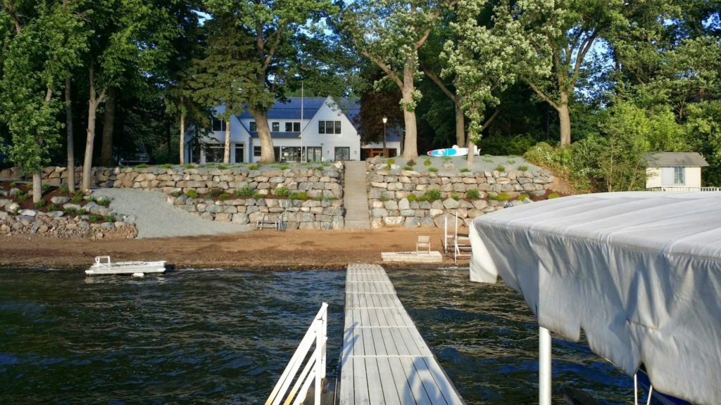 Two large tiers of fieldstone boulder walls  retain the slope on this lakefront property.