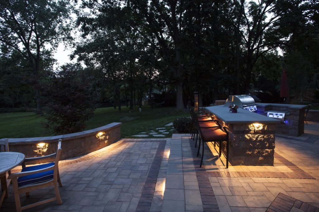 Ledge lighting illuminates steps, pathways, and bars on this unique backyard patio.