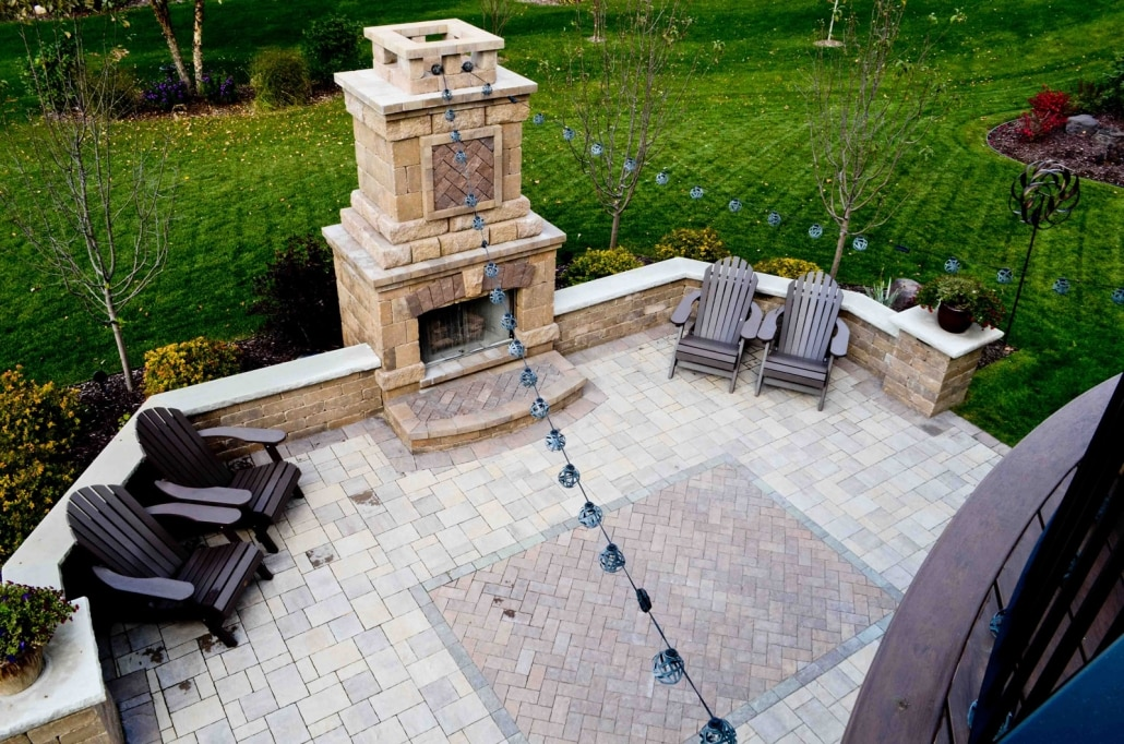 Lights and a Paver 'Rug' add personality to this outdoor fireplace and patio.