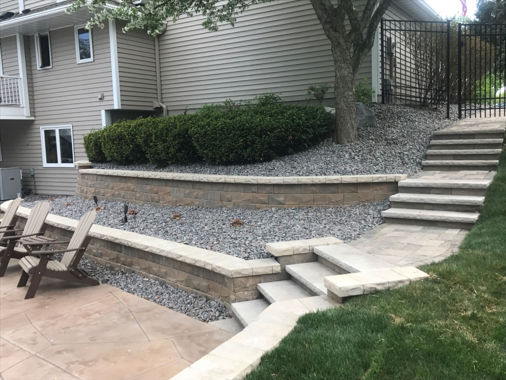 A two tiered block retaining wall and steps allow for a smooth transition to the backyard patio.