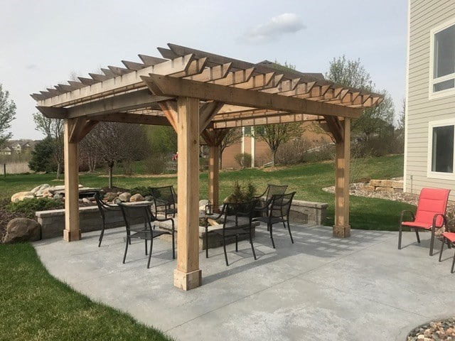 Beautiful angled battens, rafters and beams create a simple and elegant pergola over this firepit.
