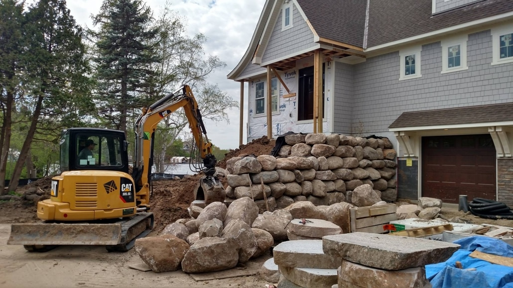 An excavator operator at Landscapes Unlimited hand selects and carefully places boulders for this retaining wall to allow for a walkout garage.
