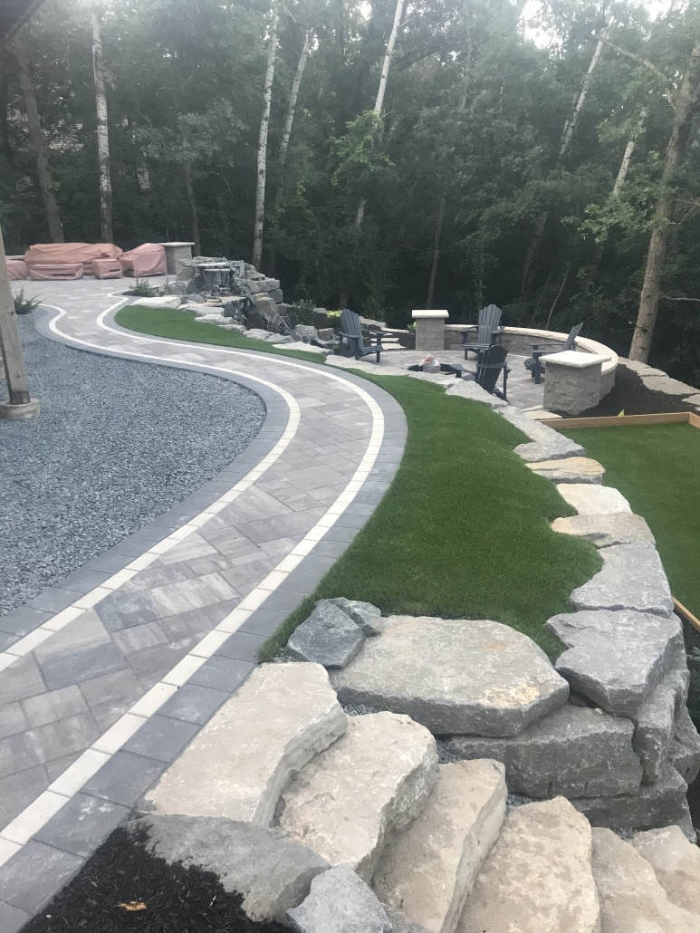 A long boulder wall near the house creates a level area for this clients patio and bocce court.