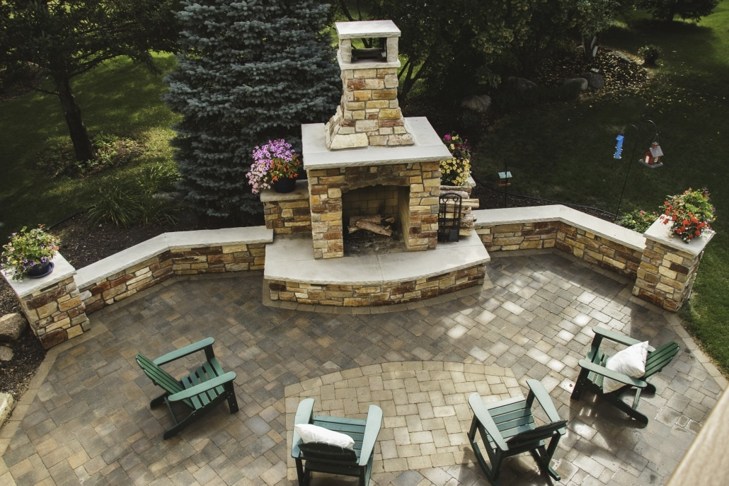 A paver inlay mimics the shape of this hearth creating unity between this patio and fireplace.