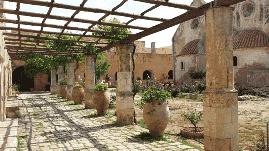 A traditional pergola covers this walkway around the edge of a courtyard.